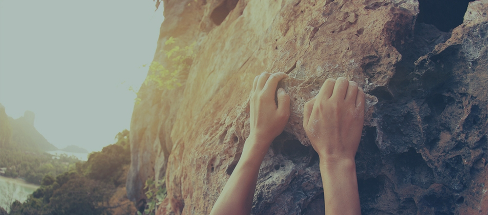 rock climber hands climbing at seaside mountain cliff rock